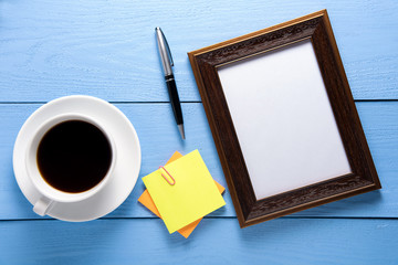 empty photo frames on wooden table with cup of coffee and post it on wooden table background