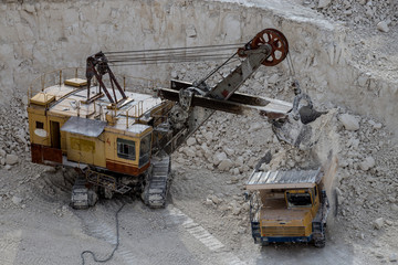 Excavator and dump truck working and extracting the chalk in a quarry