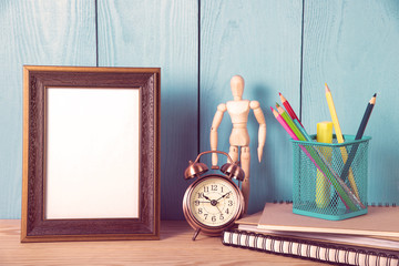 Empty photo frame with office supplies objects on wooden table
