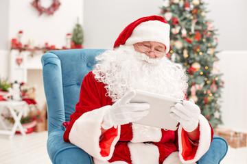 Portrait of happy Santa Claus holding Christmas letter using tab