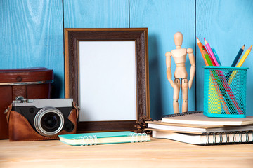 Empty photo frame with office supplies and old camera objects on wooden table