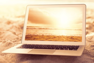 Composite image of laptop kept on sand