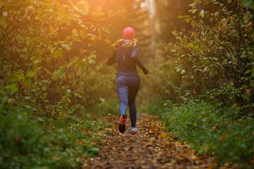 Blonde woman running among trees