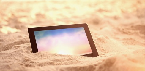 Composite image of digital tablet kept on sand at beach