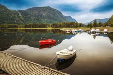 White and red fishing boats at foreground of lake landscape, scenic hill with forest at background. Norway, Scandinavia.