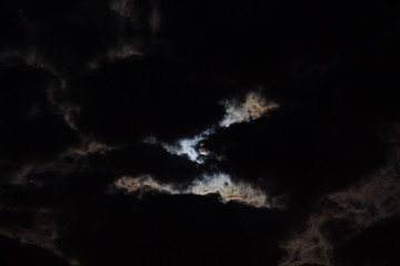 The night is dark gloomy sky. The moon shines through the clouds. Full moon. Gothic background.