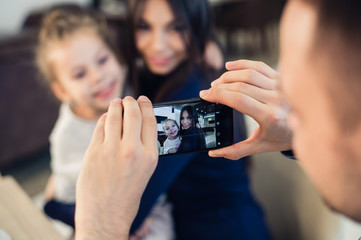 family, parenthood, technology, people concept - happy father taking photo of his little daughter and wife by smartphone having dinner at restaurant