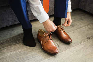The man wears shoes. Tie the laces on the shoes. Men's style. Pr