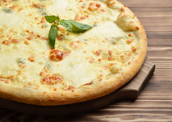 Four cheese pizza quattro fromaggi with basil leaf on a rustic w