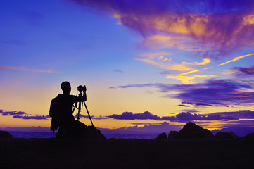 silhouette of photographer taking photo at sunset beside the sea