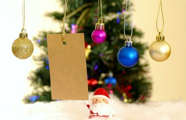 Santa Clause model and blank card with the background of decorated Christmas trees and balls