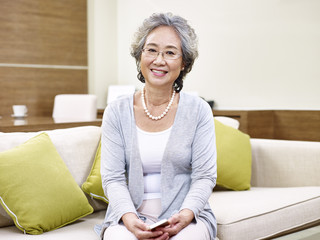 portrait of senior asian woman sitting on couch at home