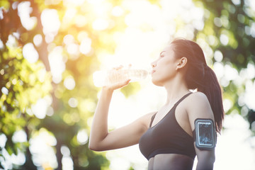 Fitness woman athlete takes a break, Drinking water, Hot day. Co