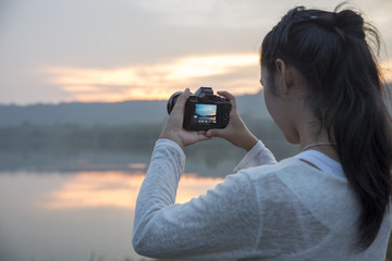 A beautiful woman holding a camera,take photo at sunset ,reservoir in Surin province,northeast of Thailand.