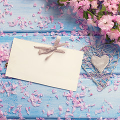 Background  with pink sakura  flowers and empty tag on blue wood
