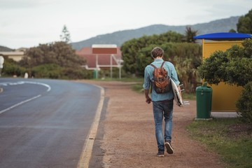 Man with backpack carrying a surfboard walking along road