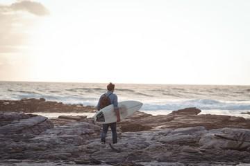 Man carrying a surfboard walking by sea