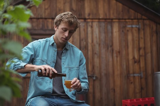 Young man pouring beer in glass