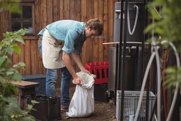 Man holding sack of barley at home brewery