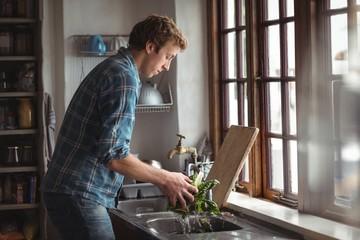 Man washing vegetable in kitchen