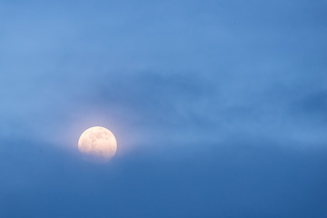 A full moon rises behind a bank of blue clouds