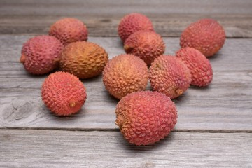 Wall Mural - Lychee, Fresh lychee and peeled showing the red skin and white flesh with green leaf on a wooden background