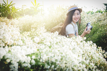 Asian hipster cute teen girl with camera in white flower garden,