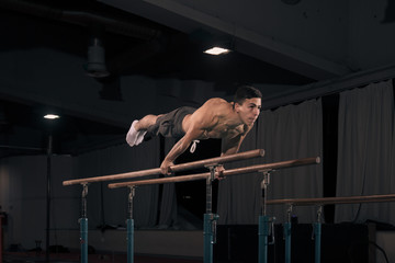 man gymanst in air, parallel bars