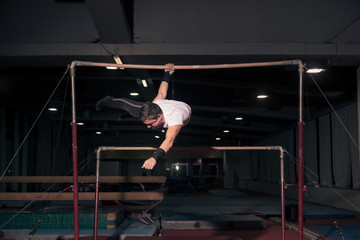 man gymnast hanging, horizontal bar