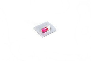 Single pink and white pill in a blister pack isolated on white background
