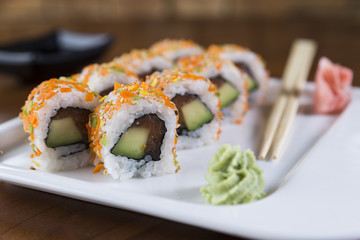 Uramaki sushi with cornflakes, avocado and tuna fish. Chopsticks and soy sauce at the background.