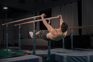 man gymnast in air, parallel bars