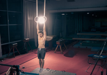 one young athlete hanging gymnastics rings