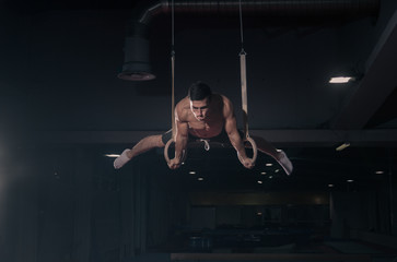 Foto op Plexiglas Gymnastiek young man gymnast, gymnastics rings in air