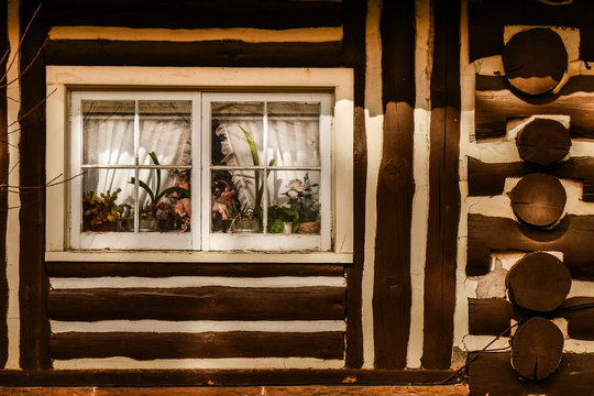 Log Cabin with Flowers in Window