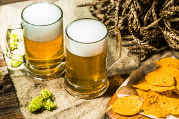Two beer mugs with hops and chips and wheat