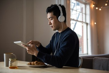 Man listening music on digital tablet