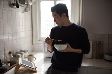 Man using digital tablet while having breakfast