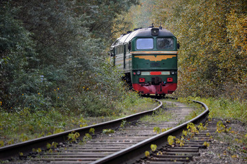 Old train traveling on the tracks in the middle of autumn forest.