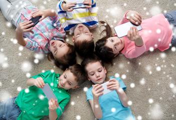 children with smartphones lying on floor