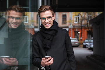 Smiling business man with phone near the building
