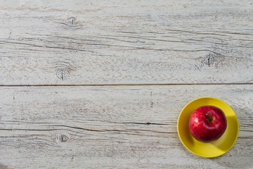 red apple on a yellow saucer on a light wooden background