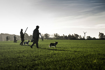 Foto op Aluminium Jacht Hunter with hunting dog walks through field