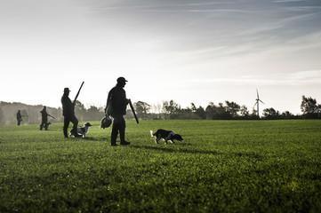 Hunter with hunting dog walks through field