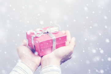 Closeup, Hand holding red gift box and snow in winter, New year holidays and greeting season concept