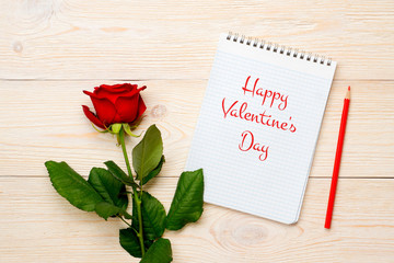 happy valentine's day greeting with red rose on white wooden tab