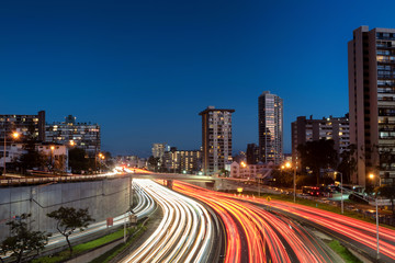 Light trails over H1 highway in downtown Honolulu, Hawaii during sunset golden hour