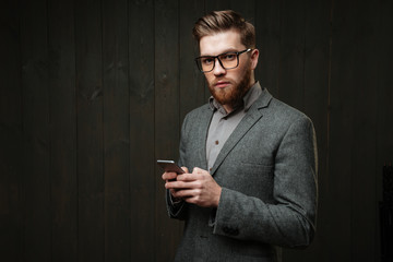 Man in casual suit and eyeglasses holding mobile phone