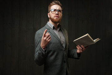 Young bearded man in eyeglasses and casual suit learning script