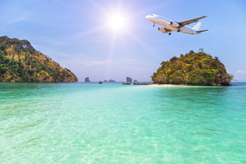 passenger airplane flying over above small island in tropical andaman sea. travel destinations concept